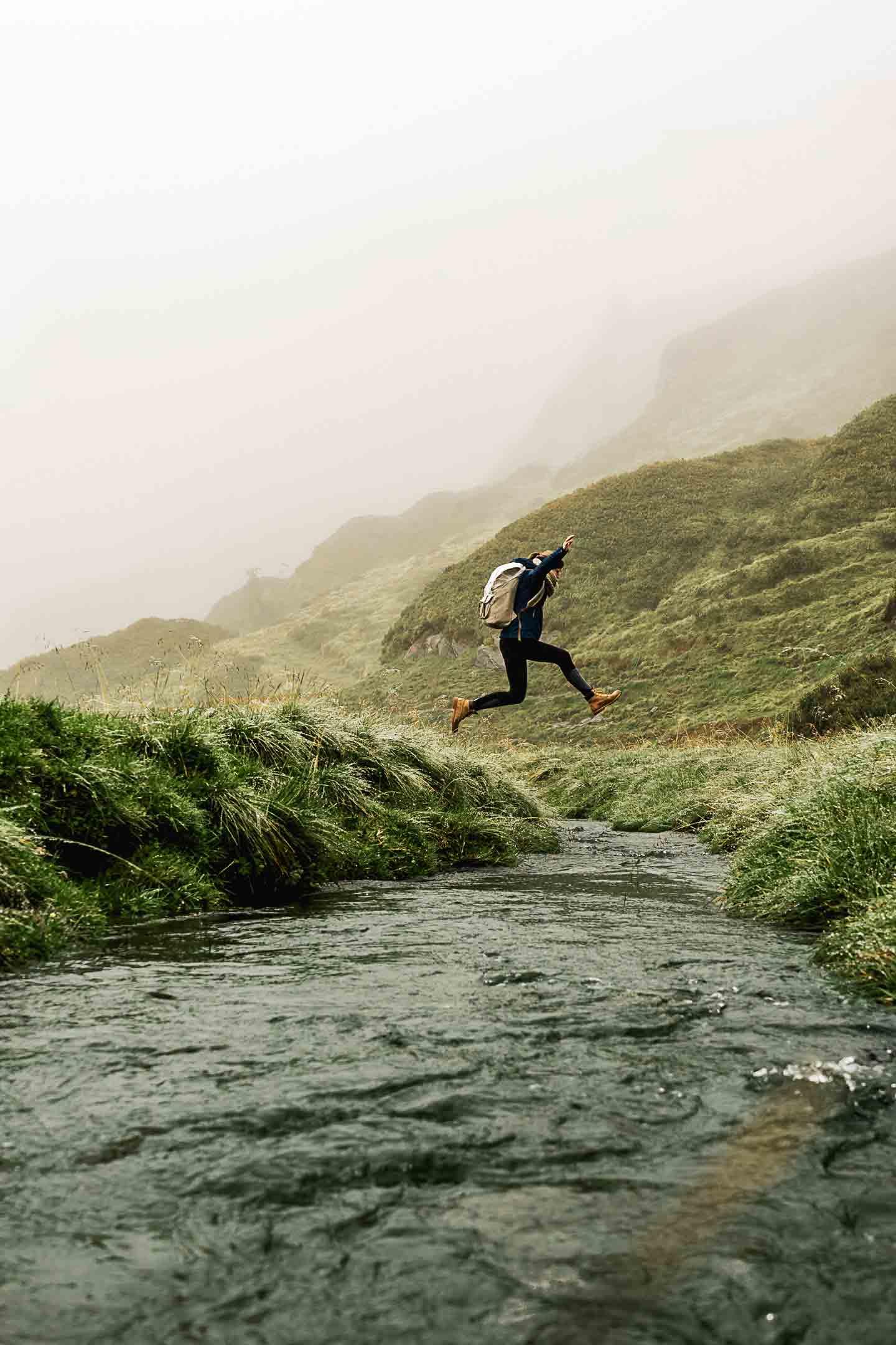 Sprung über die klaren Gewässer in den Bergen